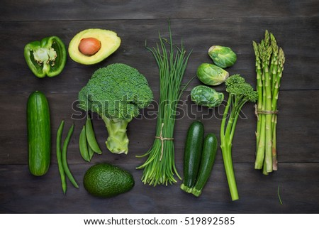 Fresh green organic vegetables on black wooden vintage table.Organic vegetables top view