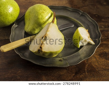 Fresh green pears on a distressed wooden table. One of the pears has been sliced and placed on a pewter plate. One of the segments has been partly eaten. - stock photo