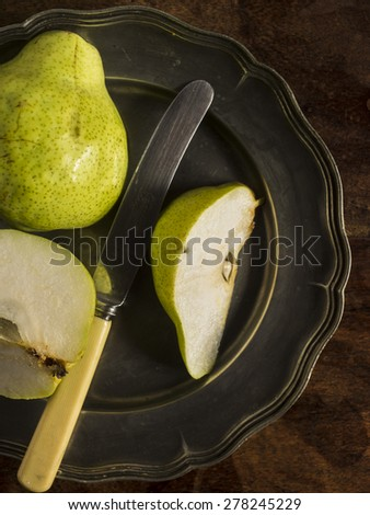 Fresh green pears on a distressed wooden table. One of the pears has been sliced with a vintage knife and placed on a pewter plate. - stock photo