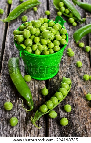 Fresh green peas in a drop of water on a wooden surface