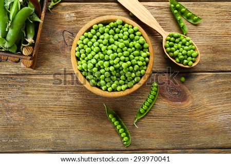 Fresh green peas in bowl and spoon on table close up - stock photo