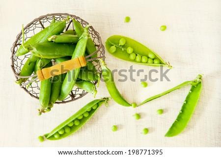 Fresh green peas in the metallic basket - stock photo