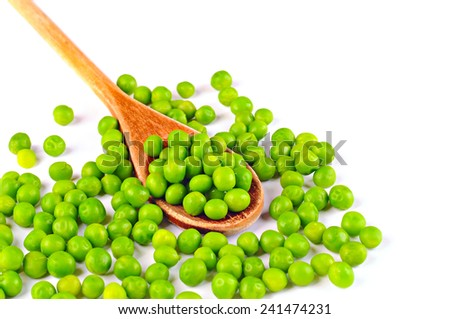 Fresh green peas on a wooden spoon and on the table, on white background - stock photo