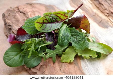 Fresh green salad mix on wooden tray. - stock photo