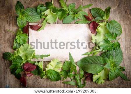 Fresh green salad on the frame of wooden background