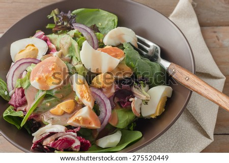 fresh green salad with boiled eggs , red onion and drizzled with balsamic vinaigrette dressing on wooden background - stock photo