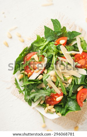 Fresh green salad with tomatoes, parmesan cheese and pine nuts