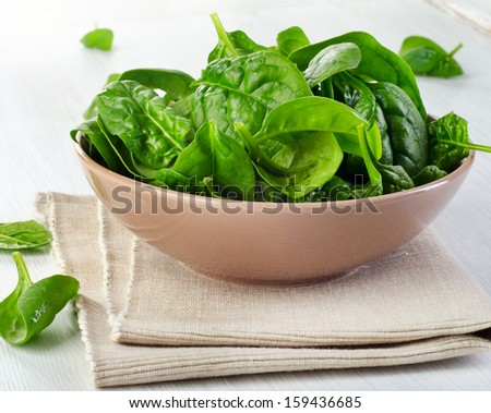 Fresh green spinach leaves on a wooden table. Selective focus - stock photo