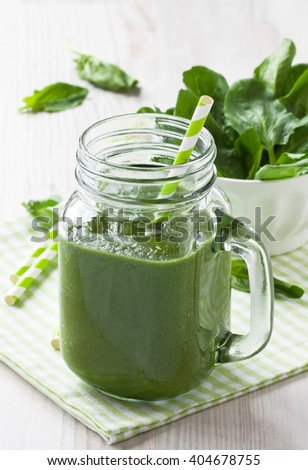 Fresh green spinach smoothie in glass mason jar with straw/Spinach smoothie   - stock photo
