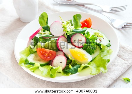 Fresh green spring vegetable salad with egg over white wooden background  - stock photo