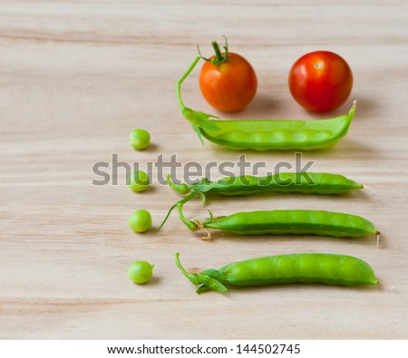 Fresh green sweet pea pod and peas and tomatoes from garden. selective focus, shallow dof - stock photo