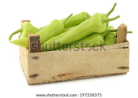 fresh green sweet peppers (banana peppers) in a wooden box on a white background