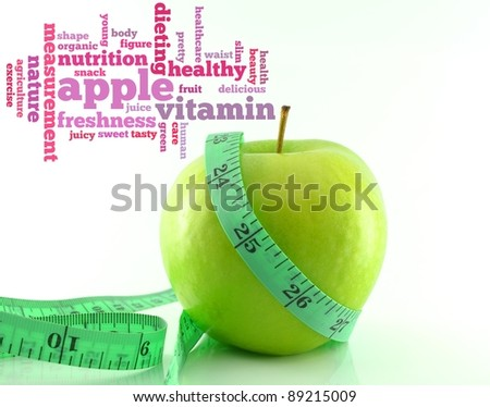 Fresh green tasty apple and measuring tape with info-text graphics and arrangement concept on white background (word cloud) - stock photo