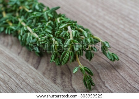 Fresh green Thyme branch on the wood background