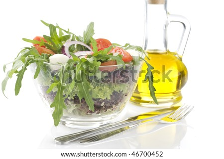 Fresh green vegetable salad with mozzarella in a transparent bowl over white background