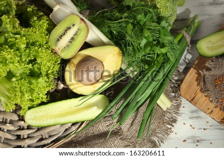 Fresh green vegetables and fruits, on wooden background - stock photo