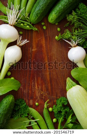 Fresh green vegetables and herbs on a dark background. food background. book cover. space for text. frame of vegetables.