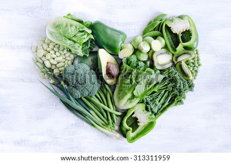 Fresh green vegetables arranged in a heart shape, broccoli, broad beans, capsicum, kiwi, avocado, beans, peas, peppers for healthy living concept  - stock photo