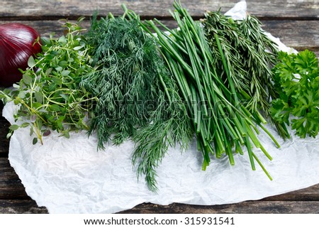 Fresh Green Vegetables. Onion, Dill, Rosemary, Parsley, Chives and thyme. on old wooden table - stock photo