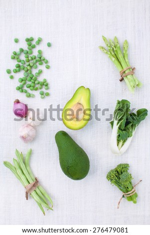 Fresh green vegetables variety on rustic white background from top view, broccoli, celery, avocado, pepper, peas, beans, lettuce, - stock photo