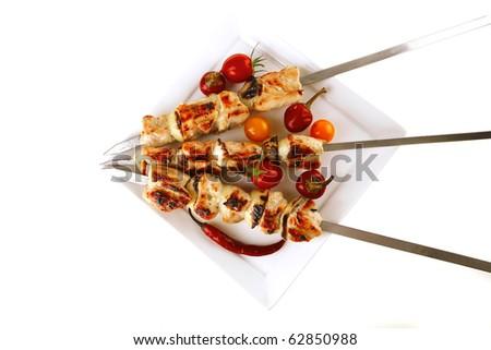 fresh grilled chicken shish kebab on white platter - stock photo