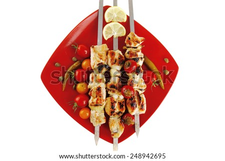 fresh grilled chicken shish kebab served wtih tomato cherry hot peppers on skewers over red plate isolated on white background - stock photo