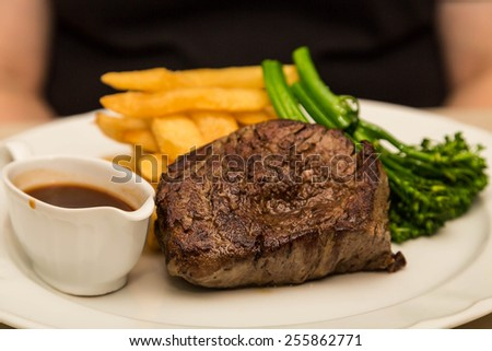 Fresh grilled fillet mignon steak with a boat of gravy, french fries and broccoli - stock photo