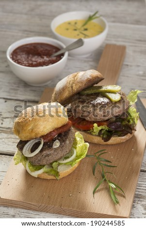 fresh grilled hamburgers with ketchup and sauce hollandaise, pickles and salad - stock photo