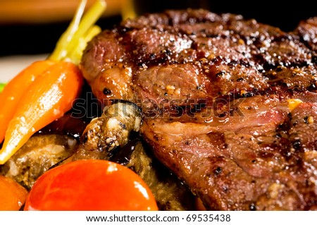 fresh grilled ribeye steak with broccoli,carrot and cherry tomatoes on side - stock photo