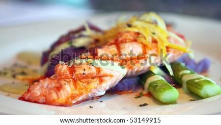 Fresh grilled salmon with purple mashed potatoes, green asparagus, lemon, and avocado vinaigrette - stock photo