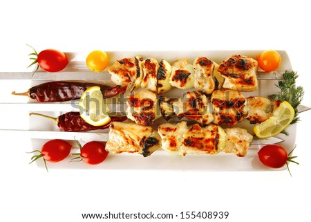 fresh grilled shish kebab on white platter - stock photo