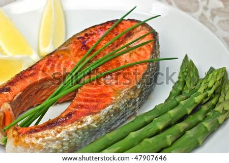 Fresh grilled sockeye salmon steak dinner with asparagus and lemon wedges - stock photo