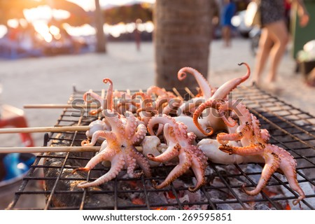Fresh grilled squids in a street shop along the shore in Thailand - stock photo