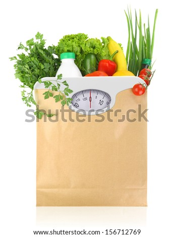 Fresh groceries in a paper bag with weight scale dial  - stock photo