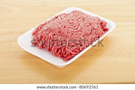 Fresh ground beef in a white polystyrene tray on a wood cutting board - stock photo