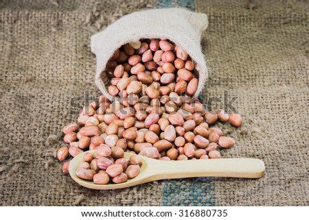 fresh ground nuts in spoon and pile on sack cloth - stock photo