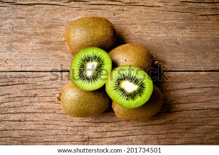 Fresh Group of Kiwi Fruits Full and Sliced on Wood Table Background, Rustic Still Life Style.