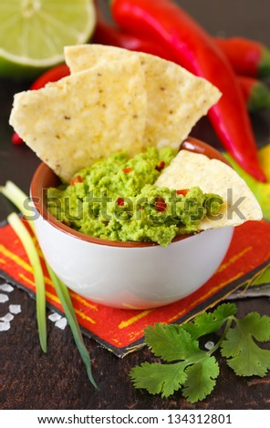 Fresh guacamole dip with nacho chips and ingredients. - stock photo