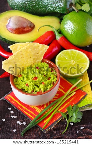 Fresh guacamole dip with nacho chips and ingredients.