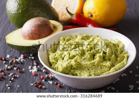 Fresh guacamole sauce with ingredients close-up on the table. horizontal - stock photo