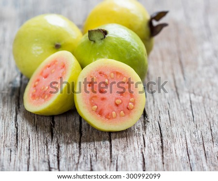 Fresh guava fruit on wooden table.