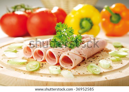 Fresh ham on a cutting board with vegetables - stock photo