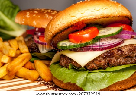 Fresh hamburger with vegetables and fries on wood background - stock photo