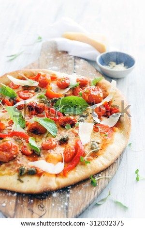 Fresh, handmade pizza with oven roasted tomatoes, peppers, capers, basil and shaved cheese  - stock photo