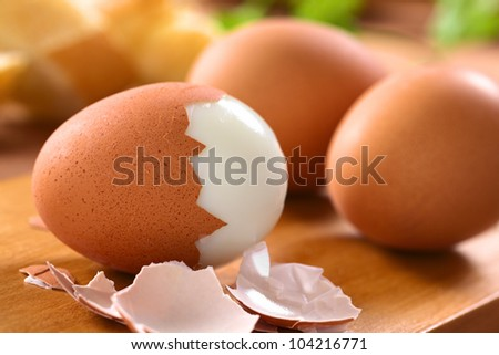Fresh hard boiled eggs with shell beside on wooden board (Selective Focus, Focus on the front of the shell on the first egg) - stock photo