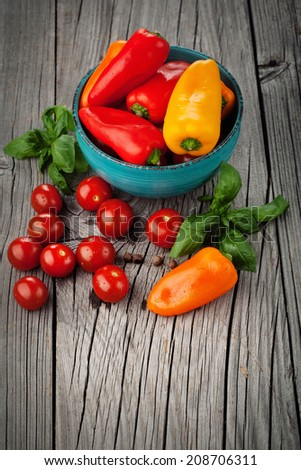 Fresh harvest of ripe tomatoes, paprika peppers and basil on old wooden background - stock photo