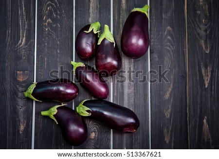 Fresh healthy eggplants on dark wooden background.