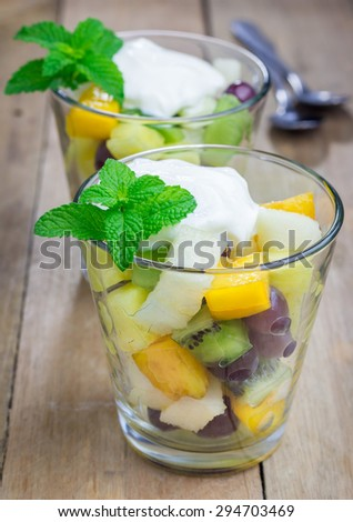 Fresh healthy fruit salad in a glass with whipping cream on top - stock photo