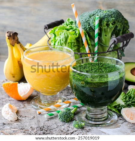 Fresh healthy green and yellow detox smoothie on wooden background with ingredients - stock photo
