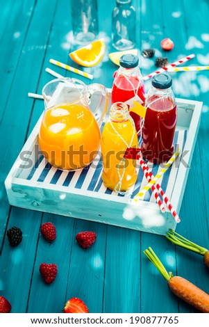 Fresh healthy homemade fruit juice squeezed from citrus, raspberries strawberries and carrots standing on a wooden tray in glass bottle on a turquoise picnic table in dappled summer sunlight - stock photo